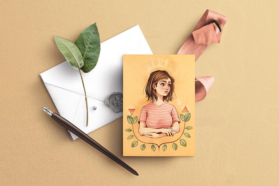 """Mock up de """"La estampa de Grethel"""" con una postal sobre un sobre, una pluma estilográfica, un lazo y una ramita de laurel."""
